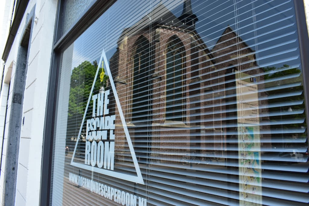 Reflectie in coronatijd - reflectie van de kerk op de ramen van the escape room